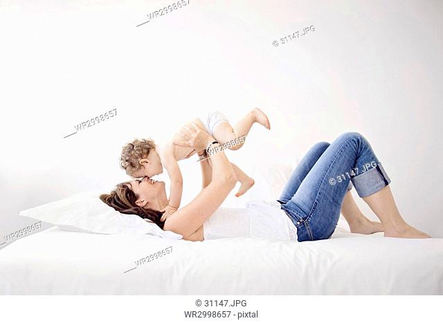 Woman with brown hair wearing jeans lying on her back on a bed, holding aloft young boy