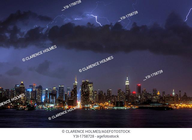 Lightning bolts illuminate the night sky over the skyline of New York City, New York, USA during a summer thunderstorm on Sunday, July 15, 2012