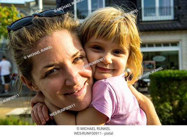 Germany, Ruegen, portrait of happy mother and little daughter head to head