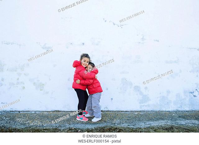 Two happy little sisters hugging each other in front of a wall