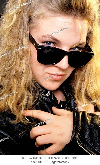 close view of model in leather jacket peering over her sunnies