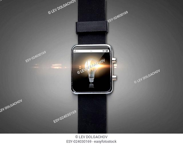 modern technology, object and media concept - close up of black smart watch with light bulb on screen