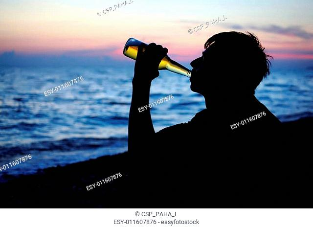 Silhouette teenager boy drinking beer on stone seacoast in evening
