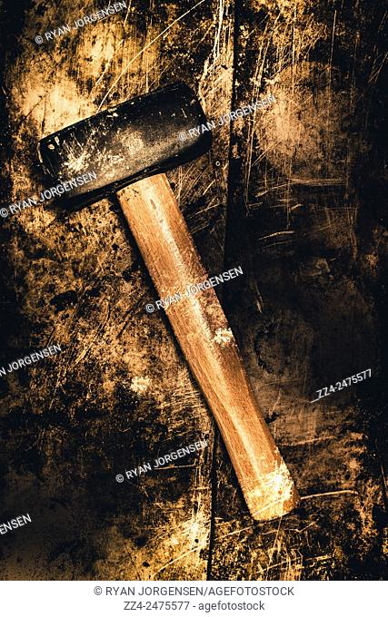 Dark dingy grunge mining mallet placed on dirty wooden background. Mine shaft mallet