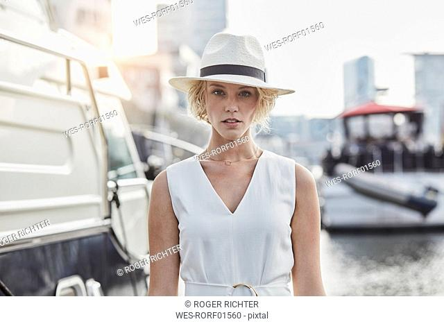 Portrait of serious young woman wearing a hat at a marina next to a yacht