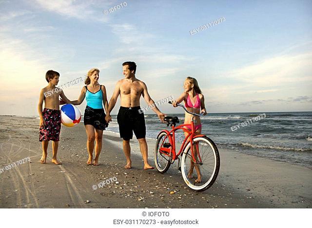 Caucasian family of four walking on beach