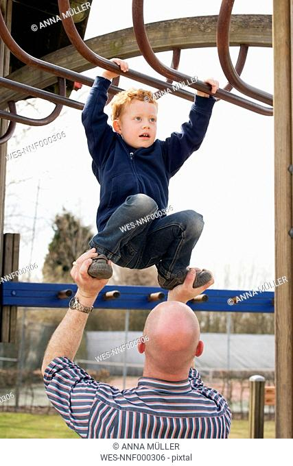 Father helping son on playground climbing on jungle gym
