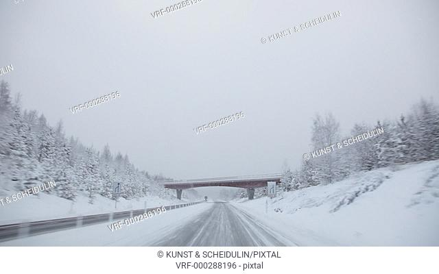 POV-shot of driving in a car on a motorway on a snowy winter day. The car passes under a bridge, meeting oncoming trucks. Västernorrlands Län, Sweden