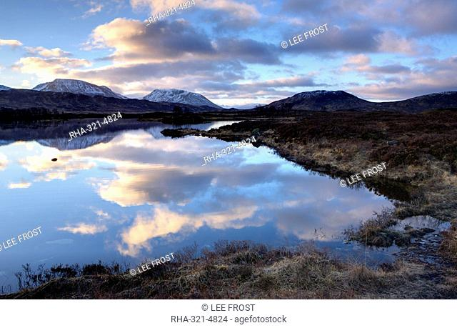 Dawn view of Loch Ba reflecting the sky and distant snow-capped mountains, Rannoch Moor, Highland, Scotland, United Kingdom, Europe