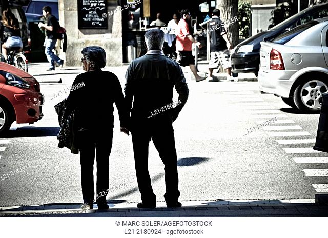 Senior couple waiting at a stoplight in a street. Barcelona, Catalonia, Spain