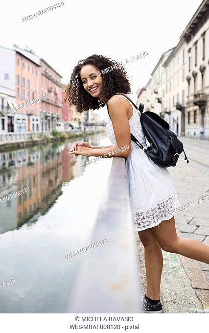 Italy, Milan, portrait of smiling young woman with backpack wearing white summer dress leaning on railing