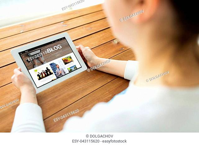 technology, people and blogging concept - close up of woman with blog page on tablet pc computer screen on wooden table