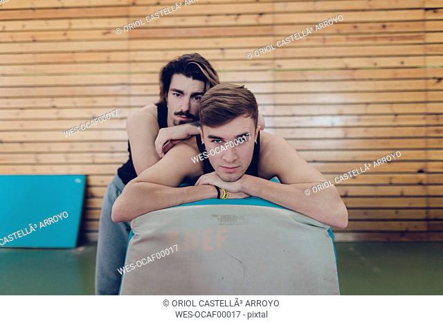 Portrait of two gymnasts resting after doing sports in gym