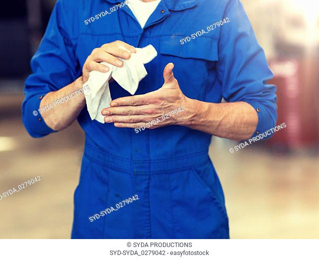 mechanic man or smith with wipe at car workshop