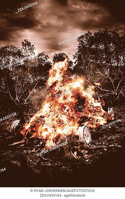 Dark creative photograph of a blazing vehicle wreckage burning into a chaotic mess of molten metal and plastic. Car bomb inferno