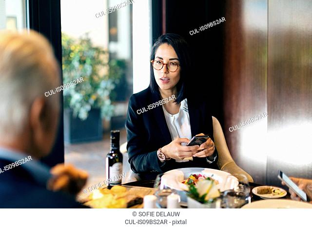 Businesswoman and man having meeting in hotel restaurant