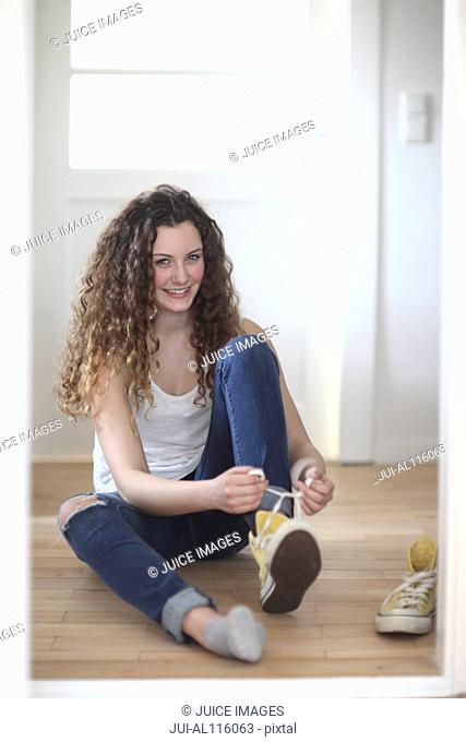Portrait of teenage girl putting on sneakers