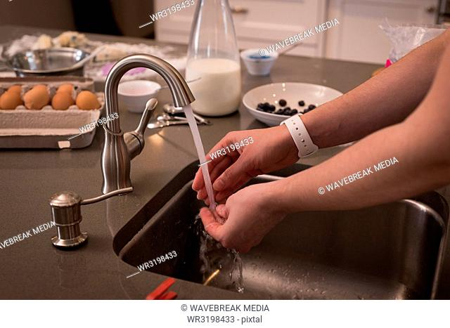 Woman washing her hands in kitchen