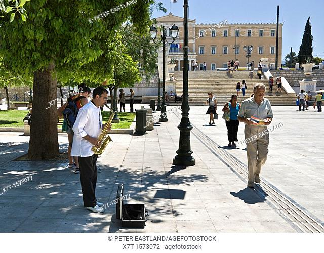A busker tries his luck in front of the parliament building in Syntagma Square in the center of Athens, Greece