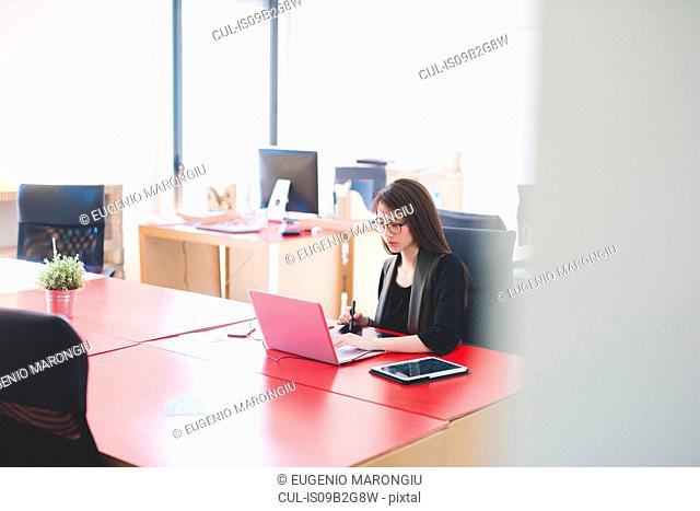 Young woman at office desk typing on laptop
