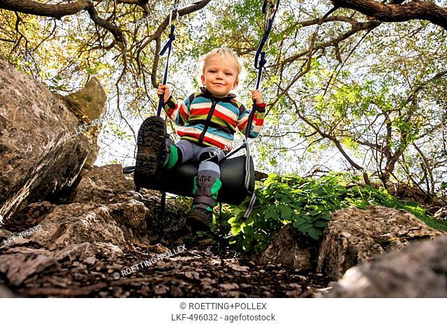 Boy (2 years) swinging, Taormina, Messina, Sicily, Italy