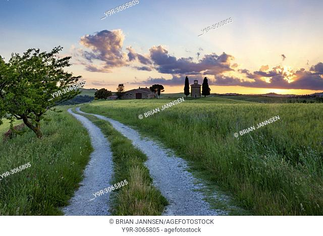 Country lane leading to Cappella di Vitaleta and the Tuscan countryside at sunset near San Quirico d'Orcia, Tuscany Italy
