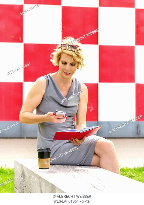 Businesswoman with personal organizer sitting on bench looking at cell phone