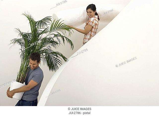 Couple moving house, man carrying large pot plant down staircase, woman carrying dust sheet, smiling