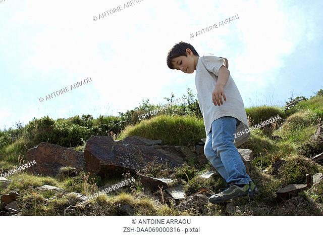 Boy standing on rocky hillside, low angle view