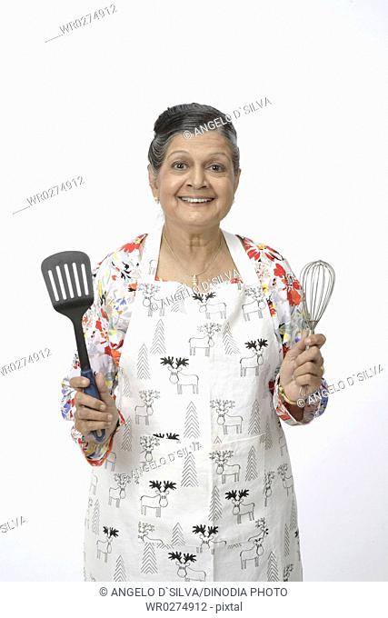 Old woman holding in one hand spatula and in other hand egg beater or hand mixer MR703A