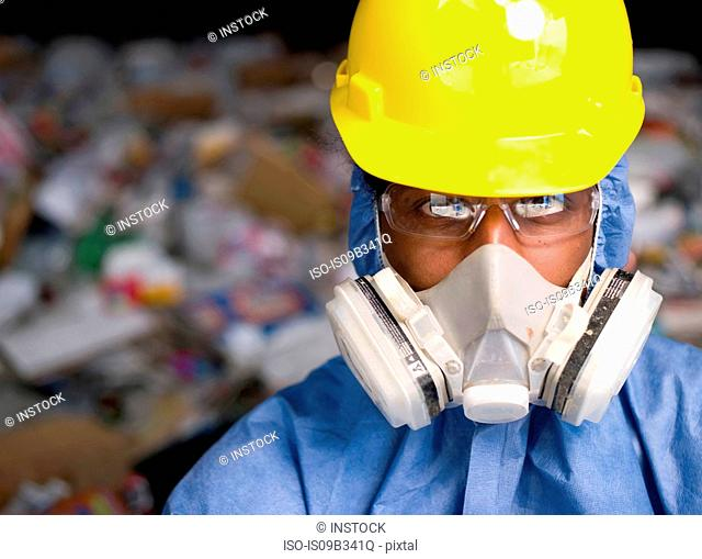 Portrait of male worker in hard hat and gas mask, in front of rubbish at recycling plant