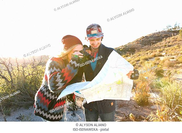 Young couple in rural setting, looking at map, laughing