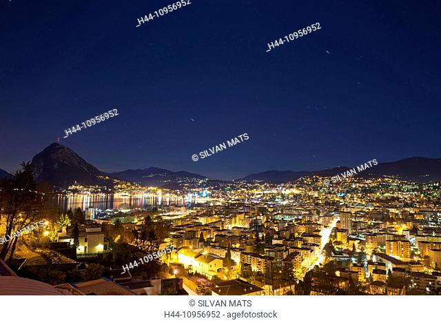 Cityscape at night close to a lake with mountain and with star trails over lugano ticino Switzerland, Europe