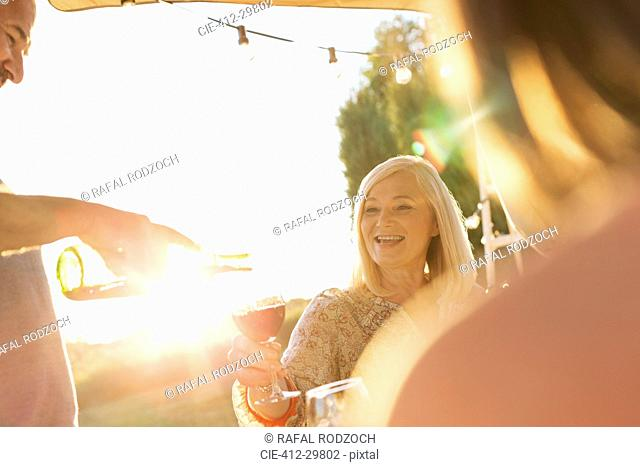 Senior man pouring wine for wife on sunny patio