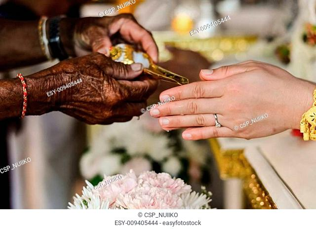 hands pouring blessing water into bride's bands, Thai wedding ceremony