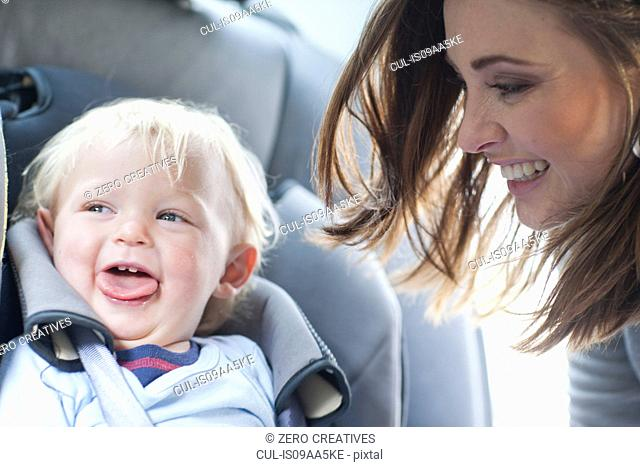 Mother with baby son in back seat of car