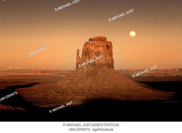 A full moon rises above a snow-covered Monument Valley, Arizona