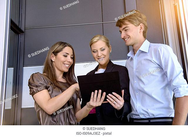 Businesswomen and businessman using digital tablet for discussion