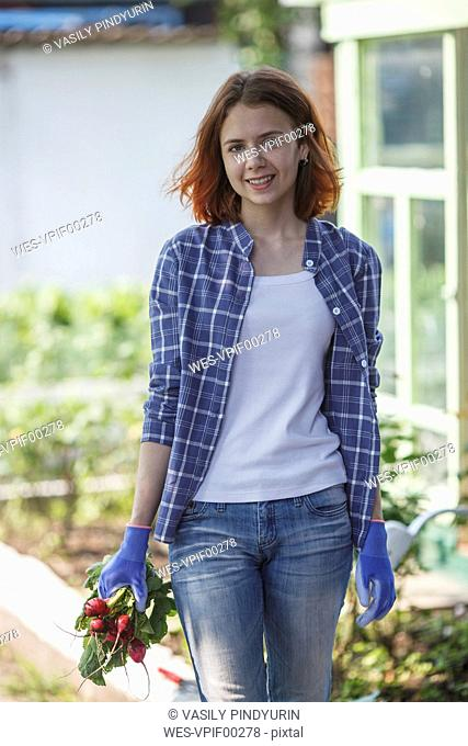 Woman holding bunch of radishes in a garden