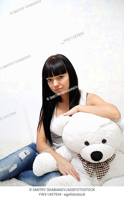 pretty brunette girl indoors embracing with big teddy bear on sofa