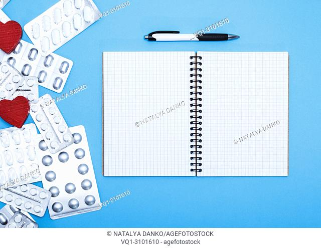 open notebook in the cell with empty white sheets and a pen, side of the package with white tablets, top view