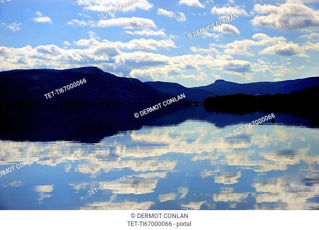 Symmetrical view of blue sky and clouds reflecting in lake