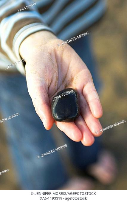 A young boy's sandy hand holds a shiny wet black stone