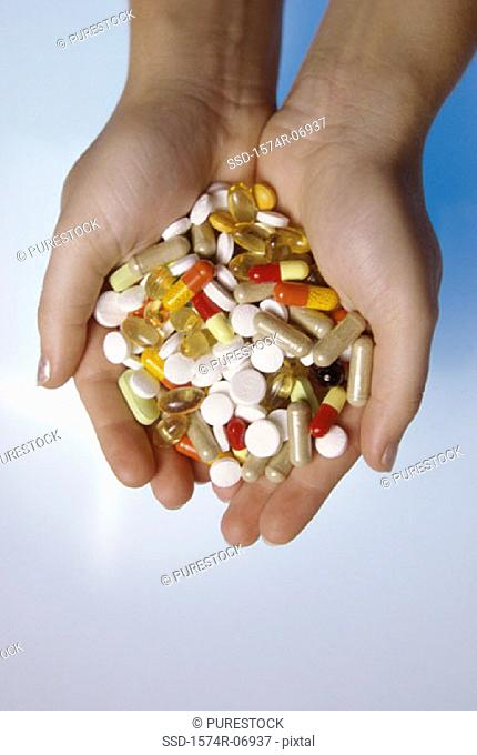 Person's hands holding an assortment of tablets and capsules