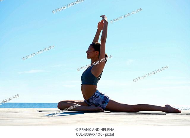 Side view of woman on pier, arms raised in yoga position