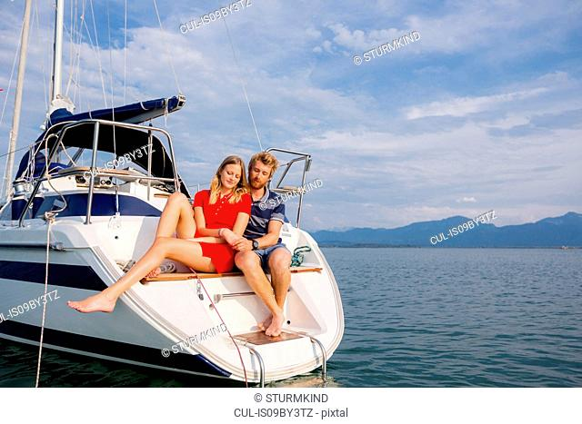 Young couple sitting on sailboat on Chiemsee lake, Bavaria, Germany