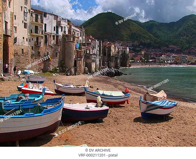 Boats on a beach next to the ocean and houses in Cefalu, Italy