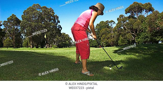 Casual young woman playing golf