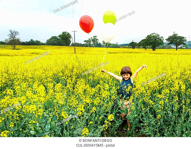 Boy standing in yellow flower field holding red, yellow and white balloons