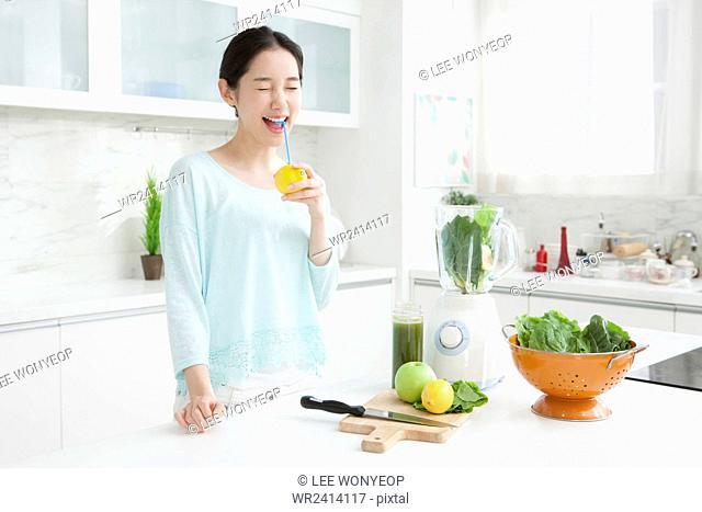 Young woman drinking lemon juice